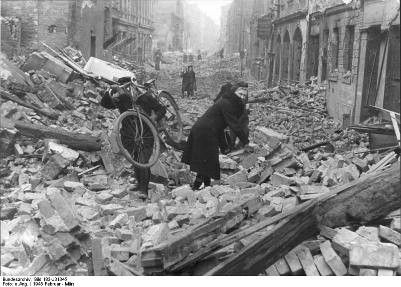 Berliners stumble through the rubble of the city following an Allied air attack in February 1945
