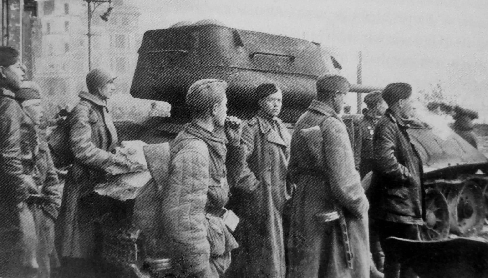 Red Army soldiers and officers at the wrecked T-34-85 tank in front of the Moltkebrücke bridge in Berlin