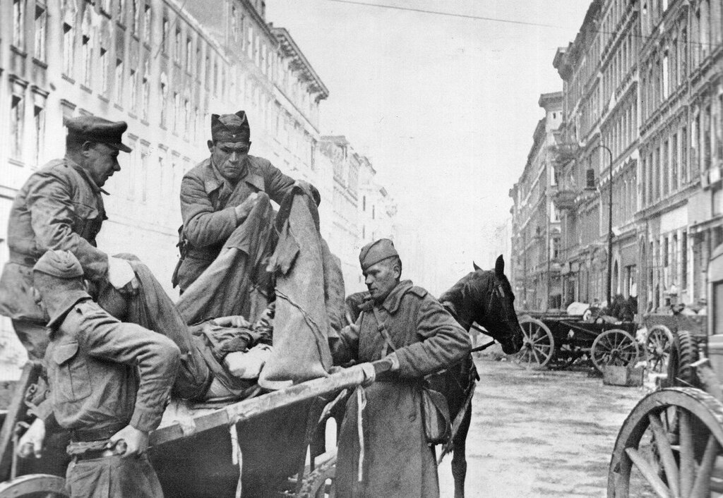 Soviet orderlies shift from a stretcher to a wagon of a wounded soldier