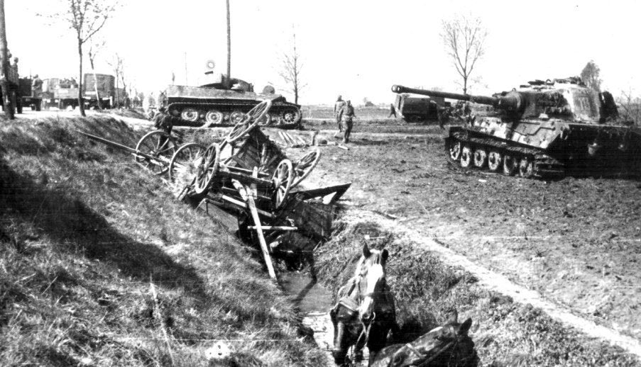 A Soviet convoy passes a destroyed German Tiger I and a Tiger II tank at Seelow Heights, 1945