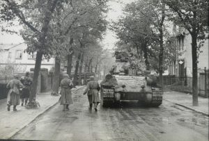 Red Army troops advance into Berlin's suburbs alongside a Soviet tank