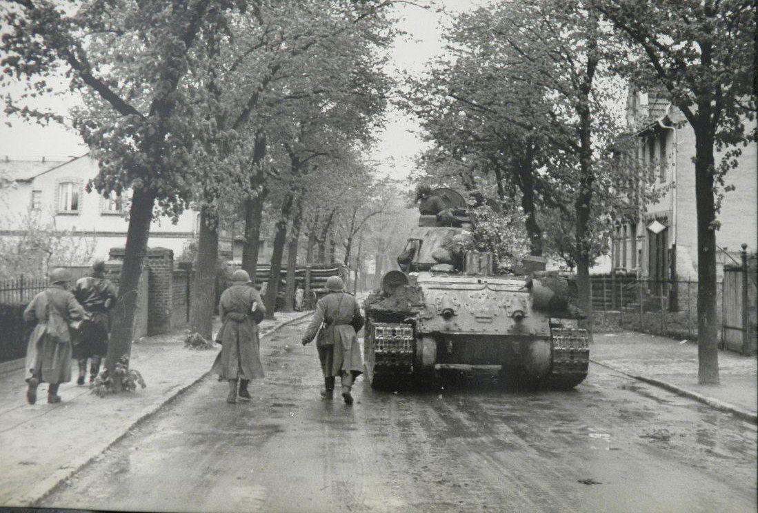 Red Army troops advance into Berlin's suburbs alongside a Soviet tank