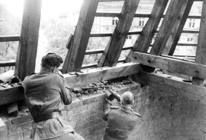 Soviet troops take up position in the roof of a building to advance through the city streets