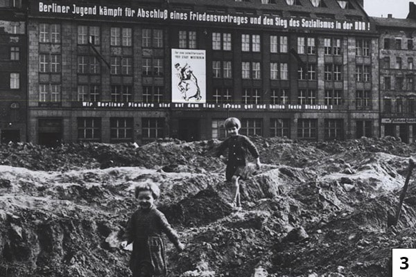 "Children play in the Soviet-controlled section of Berlin circa 1958. The signs in the background include slogans promoting socialism and an East German youth group called Berlin Pioneers. From the CIA booklet ""A City Torn Apart: Building of the Berlin Wall.""/Public Domain"