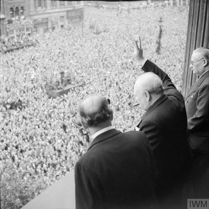 Churchill waves to crowds in Whitehall on the day he broadcast to the nation that the war with Germany had been won